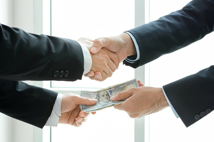 Two men shake hands as one hands over money.
