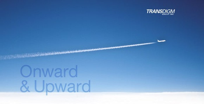 Jet with contrail flying across sky, with TransDigm logo and slogan