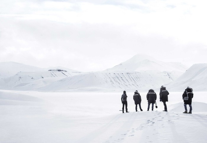 Five people wearing parkas standing on a snowy bank