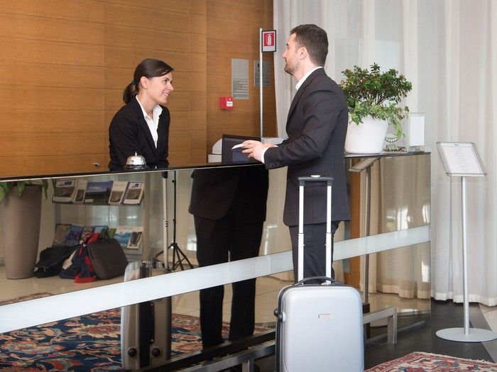 Man standing at hotel check-in talking with clerk