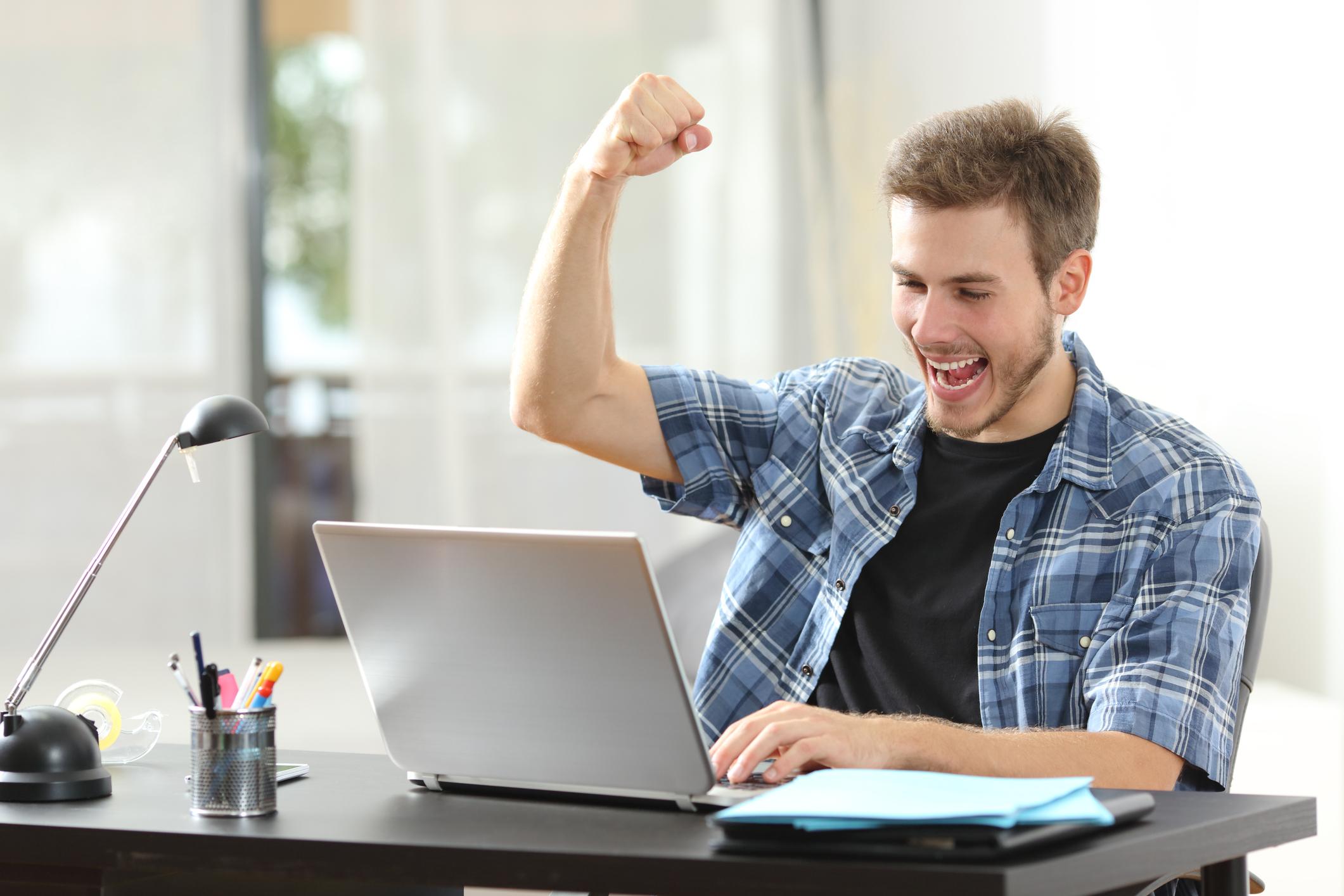 Man cheering looking at laptop screen.