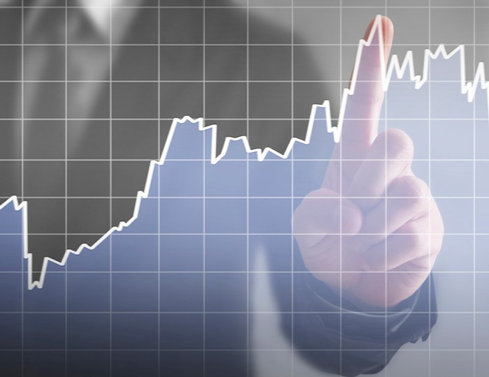 Hand pointing to rising stock graph.