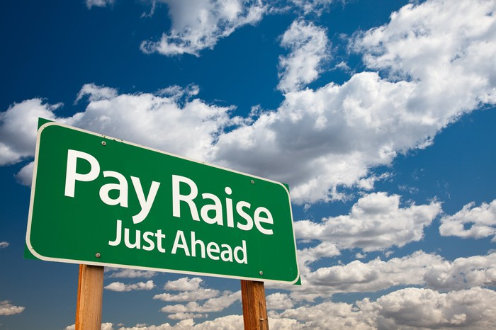 Road sign saying pay raise just ahead