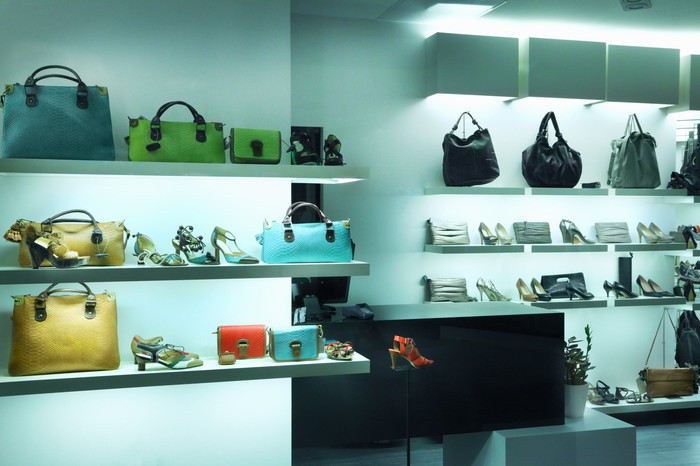 Luxury handbag store with shelves of product.