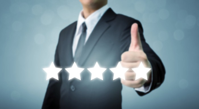 Man in suit giving thumbs up above a row of five stars