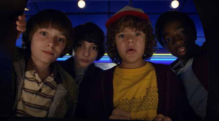Stranger Things 2 characters Will, Mike, Dustin, and Lucas with shocked expressions looking into the camera.
