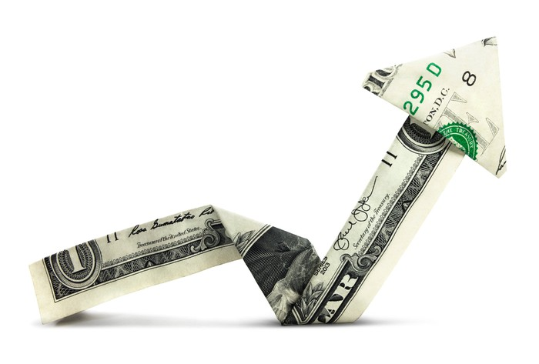 A one dollar bill folded in the shape of an arrow pointing upward.