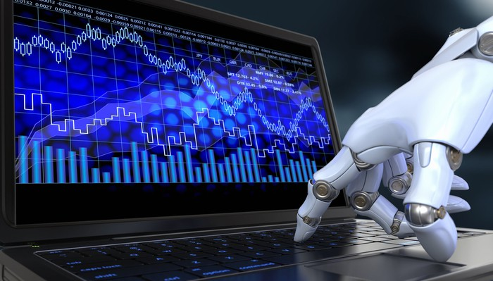 Robot hand pushing keys on a laptop, whose screen is showing a melange of charts and trend lines.