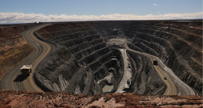 Open pit mine with trucks and other equipment running through it.