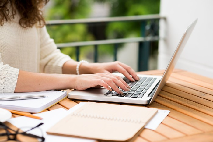 Woman typing on a laptop outdoors.