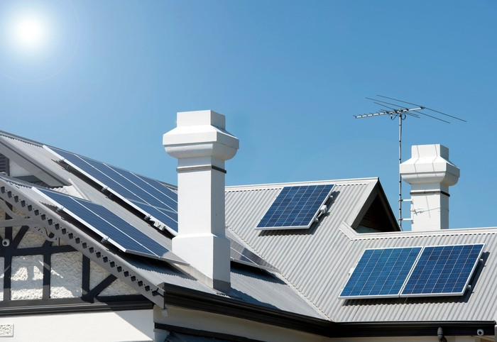 Several solar panels installed on multiple facets of a residential roof.