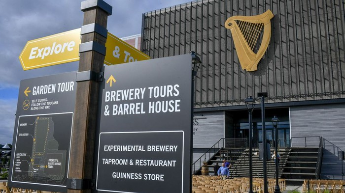 An outside view of Guinness new brewery. Guinness' harp-shaped logo is displayed on top of the building, and signs with directions are displayed in the foreground.