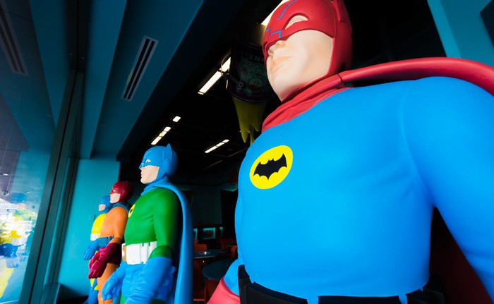 Colorful Batman and Robin mannequins displayed in headquarters window.