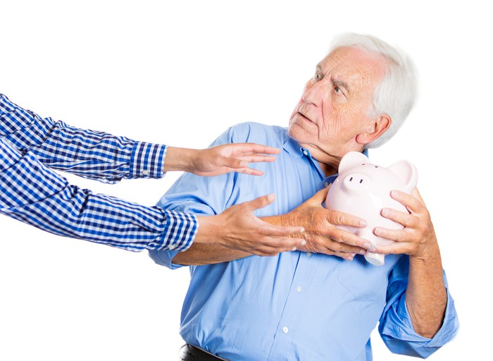 A surprised senior man tightly clutching a piggy bank as outstretched hands reach for it.