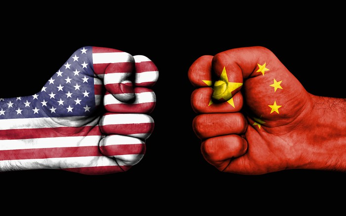 Two clenched fists, one which is decorated as the American flag, and the other as China's flag, squaring off.
