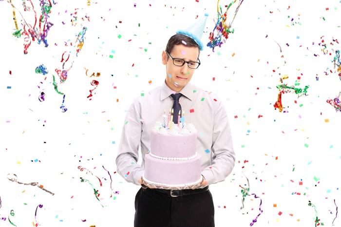 Sad man holding a cake at a party.