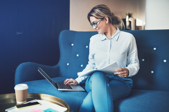 A woman types on a laptop sitting on a couch.