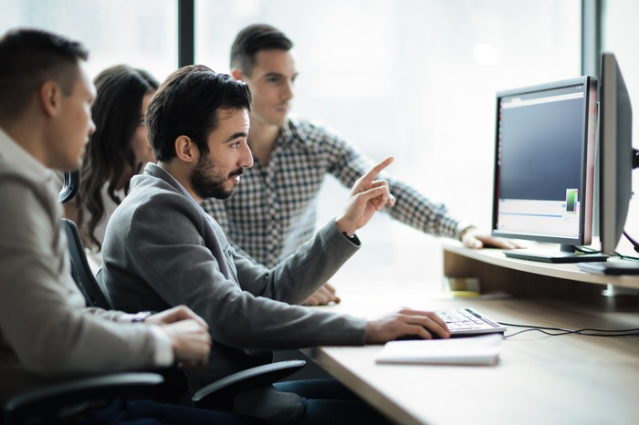 Multiple software engineers looking at two computer monitors