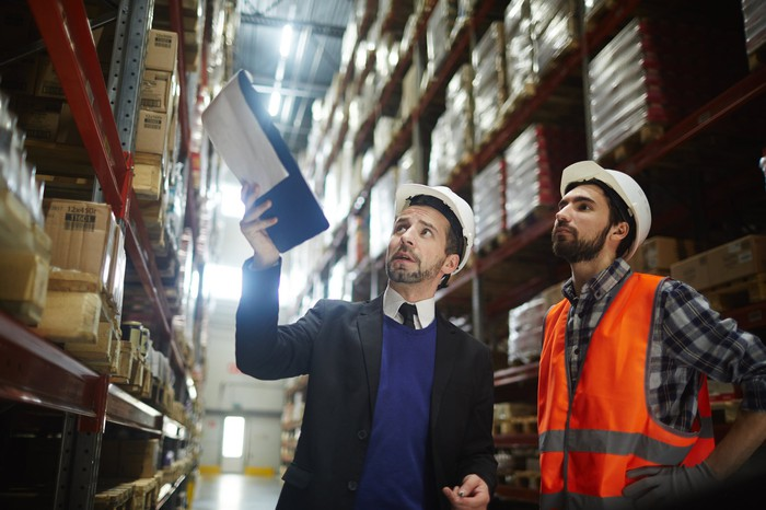 Two men in warehouse looking at shelved product.