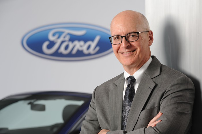 Ford CFO Bob Shanks is shown standing in front of a Ford Mustang and a white backdrop with Ford's logo.