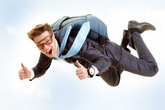 A man in a suit falling in the sky while wearing a parachute.
