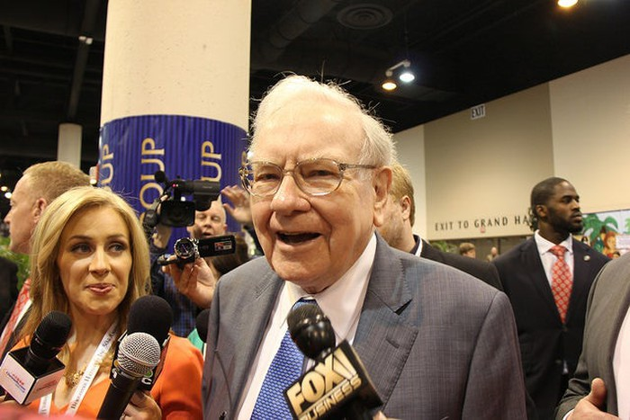 Warren Buffett speaking to reporters while walking among a crowd at an investor conference.