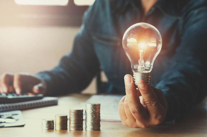 A man using a calculator while holding a light bulb in front of an ascending stack of coins