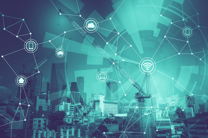 An artist's illustration of a smart city. A city skyline is connected with illustrated dots showing various devices and data getting shared across an internet connection.