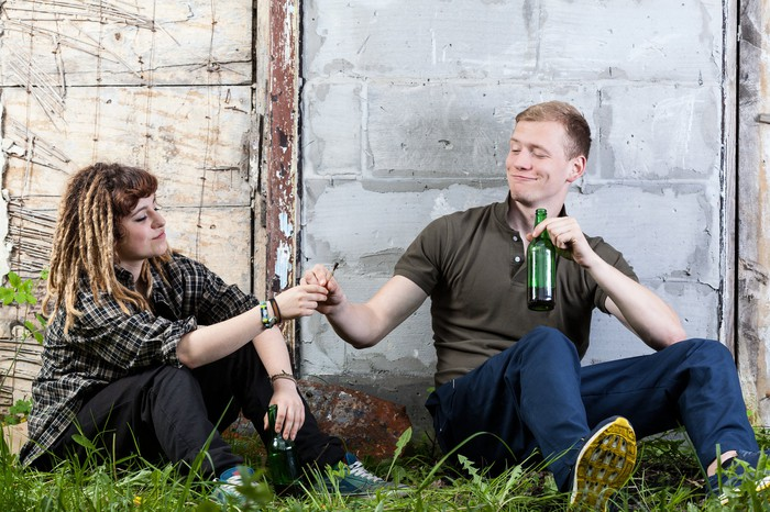A man and woman sharing beer and marijuana outside.