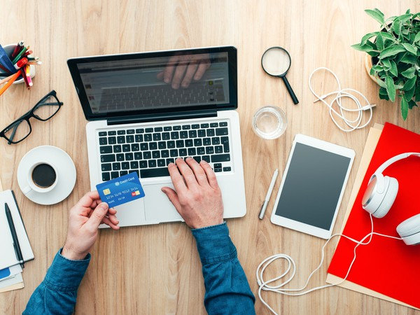 Man Working at Desk, Purchasing Item With Credit Card Online