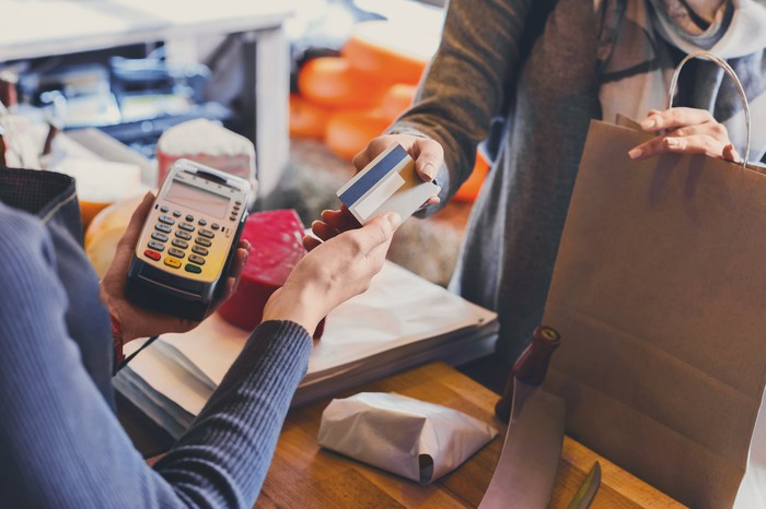 Customer hands over credit card to a clerk holding a credit card reader at the point of sale to make a purchase.