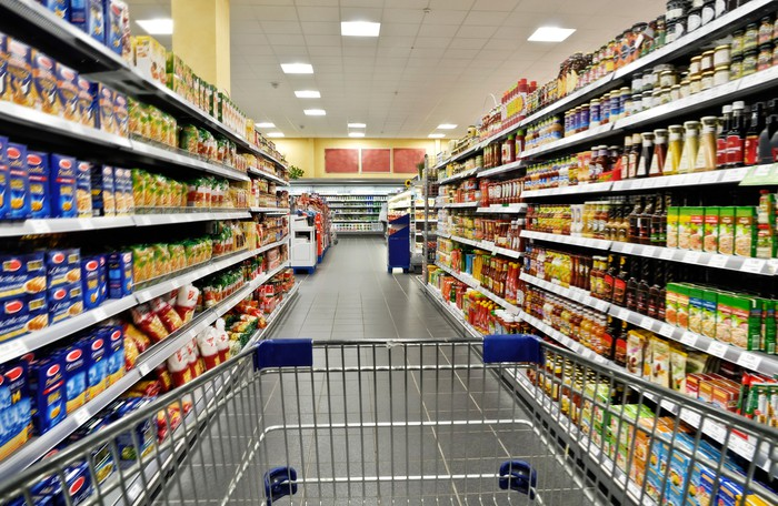 View of a grocery store aisle from the perspective of someone pushing a metal shopping cart.