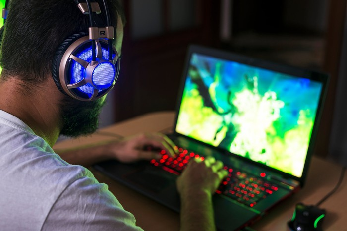 A gamer plays a video game on a laptop.