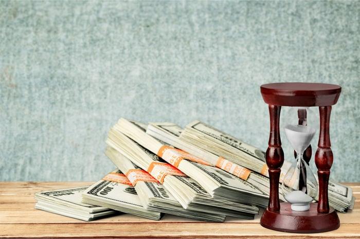 Stacks of dollar bills next to a burgundy sand timer