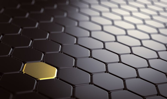 A surface comprising hexagons that are all black, except for one colored gold.