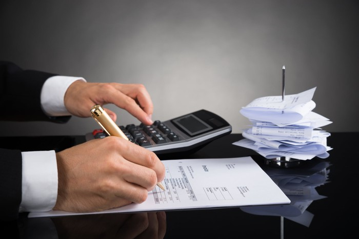 A person using a calculator and going over an invoice at a desk.
