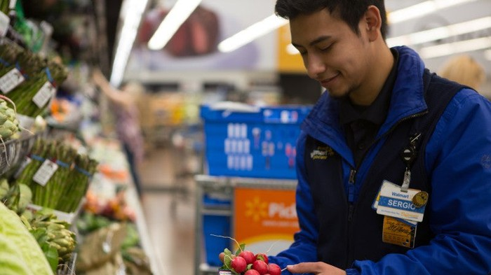 A Walmart employee placing vegetables on display.