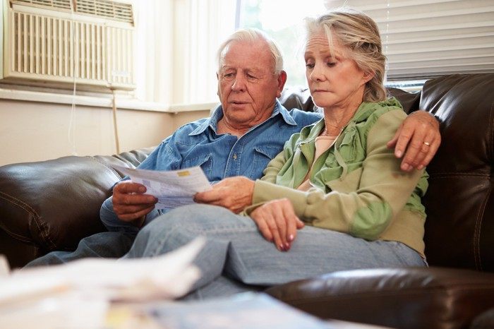 Senior man and woman on a couch looking at documents with concerned expressions.