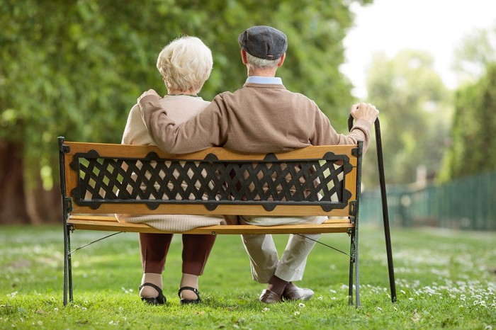An older man and woman sitting on a park bench.