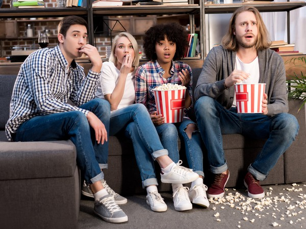 Four young people eating popcorn, watching movie with shocked expressions
