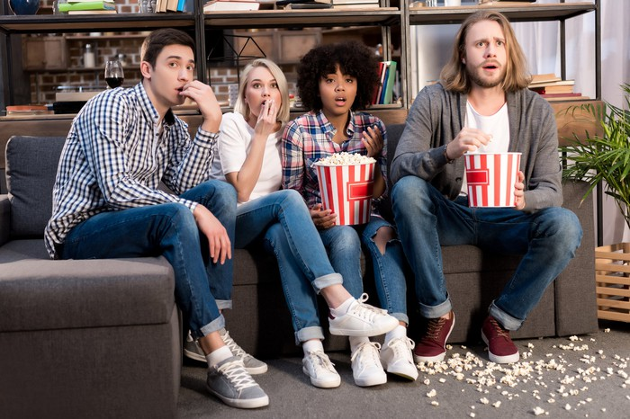 Four young people with shocked expressions are eating popcorn and watching a movie.