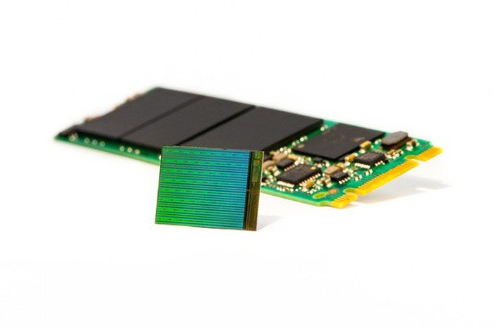 An Intel solid-state drive in the back with a NAND flash memory chip in the foreground.