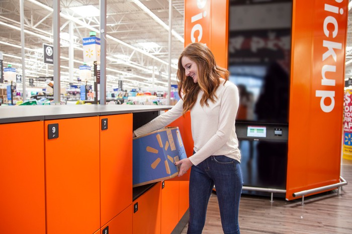 A woman removing a package from a locker at the Pickup Tower.