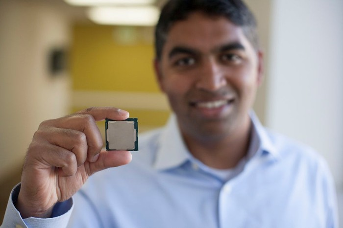 Intel executive Anand Srivatsa holding an eighth-generation Core processor, with the processor in focus