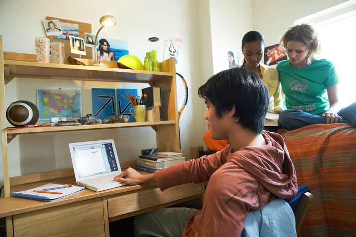 Young male at a laptop with two young females behind him who appear to be studying