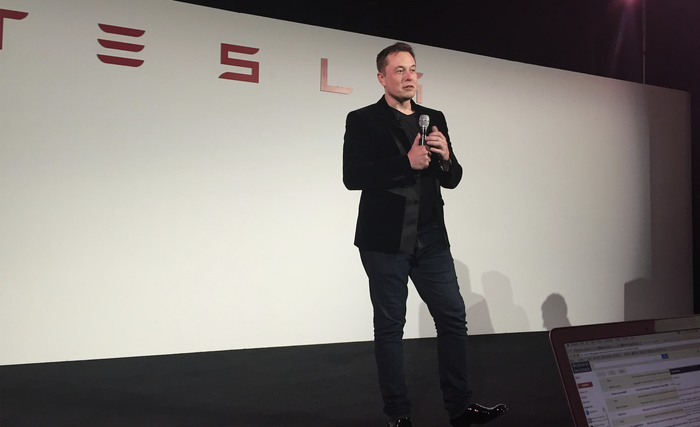 Elon Musk is standing on a stage holding a microphone and talking to an audience.