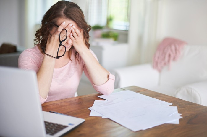 Woman sitting by a laptop and pile of papers covering her eyes