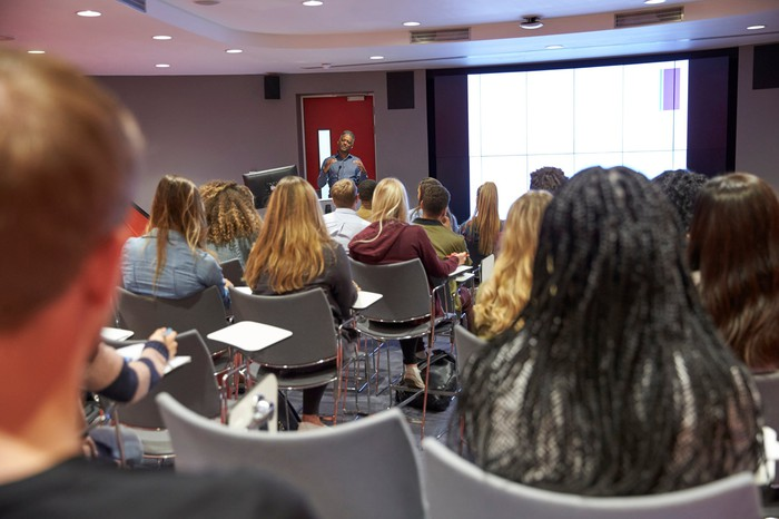 Students in a class room looking at a projector screen and professor.