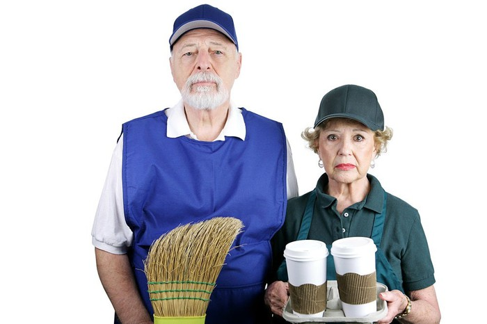 Older man in a custodian uniform with a broom, and older woman in a fast-food worker uniform holding to-go coffee cups