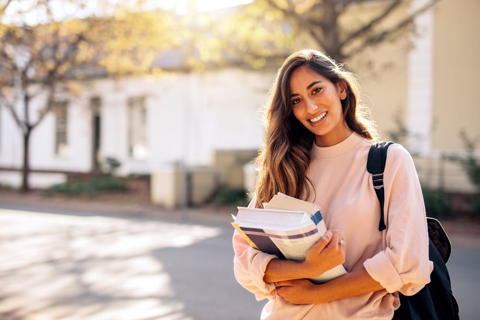Smiling young female with backpack holding books